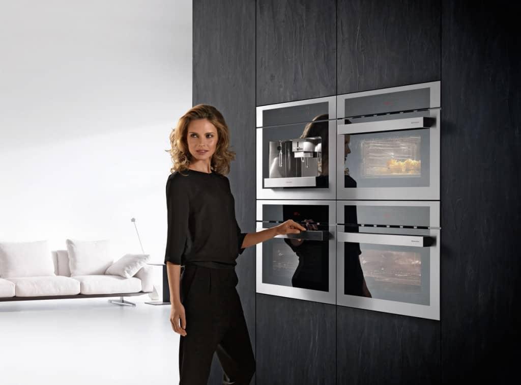 אישה עומדת לצד תנורי אפיה